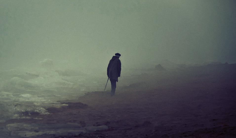 Старик на берегу реки зимой